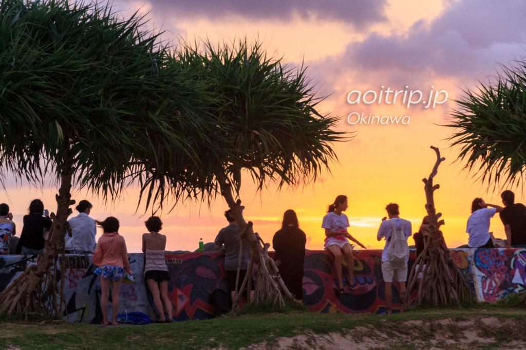 北谷サンセットビーチに腰掛けて夕日を眺める観光客